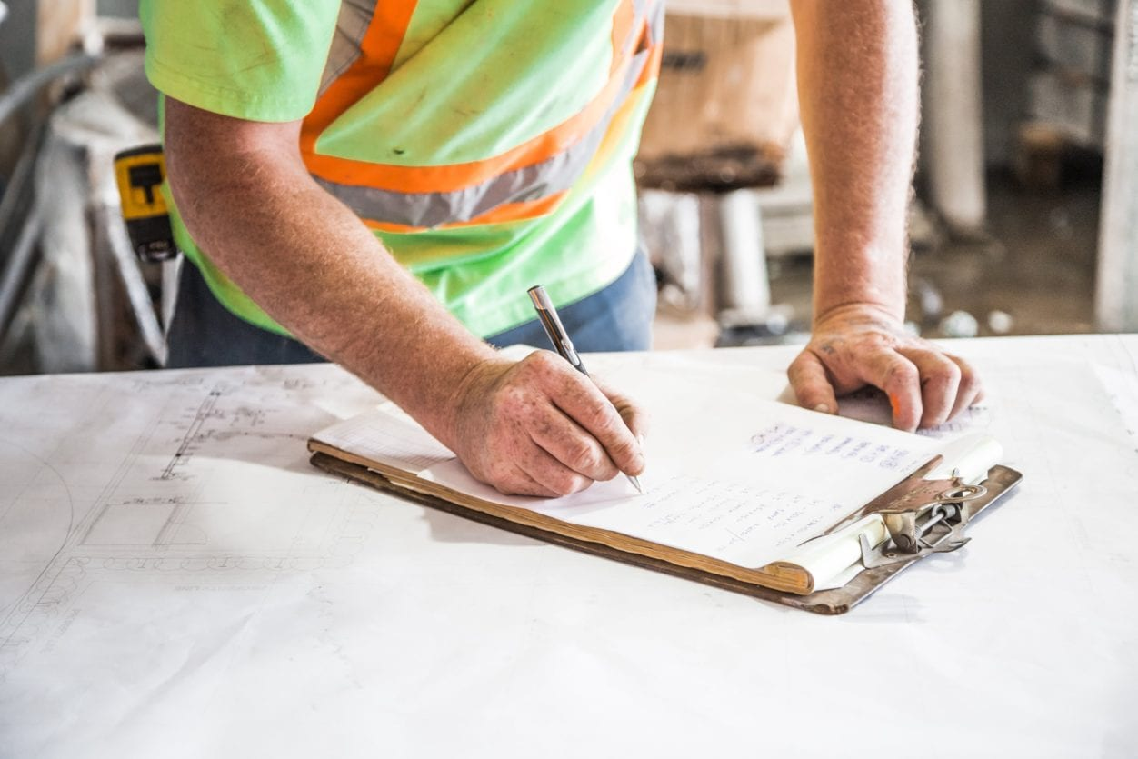 Construction worker with clipboard highlighting Fixed Price Construction Contracts