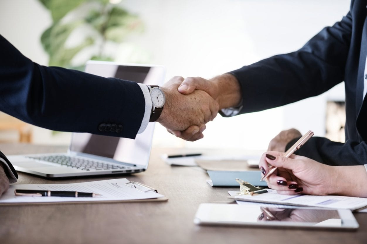 Business men shaking hands at an office, determining if mediation right for you