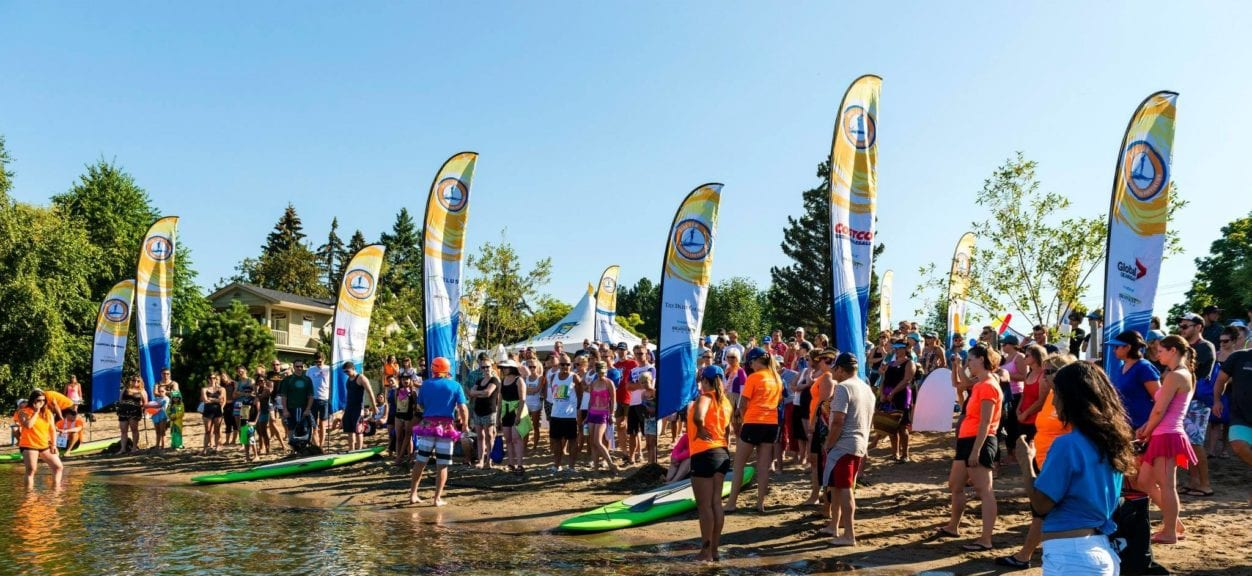 Pihl Law Paddle for Prevention Beach with signs and paddlers
