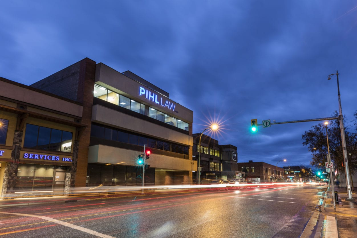 Pihl Law Office Building at Night with traffic light flares and wet road