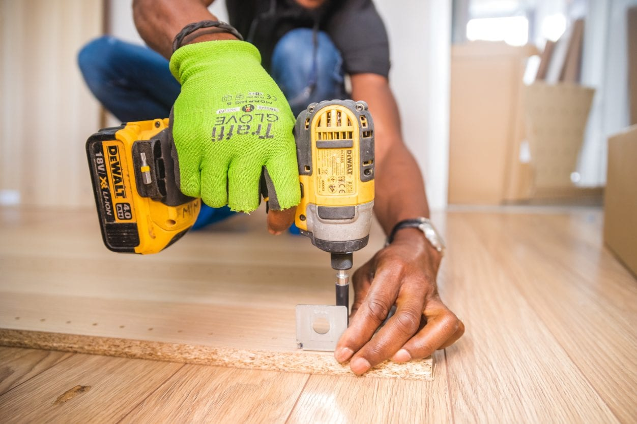 carpenter contractor working in a house closeup of hands on a drill, highlighting Tenant Created Builder's Liens for unpaid work on a rented property