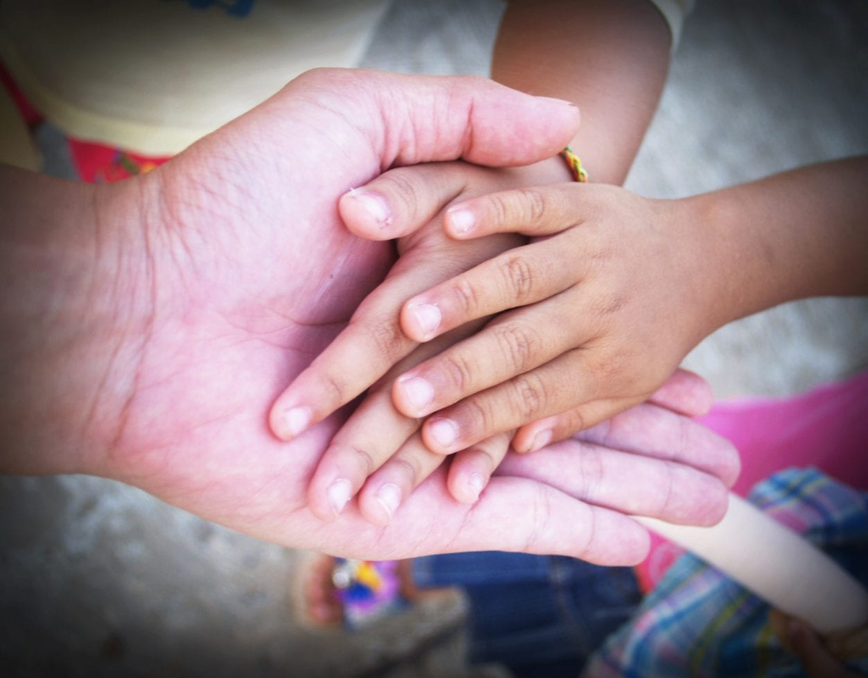 Adult hand holding childs highlighting charitable donations