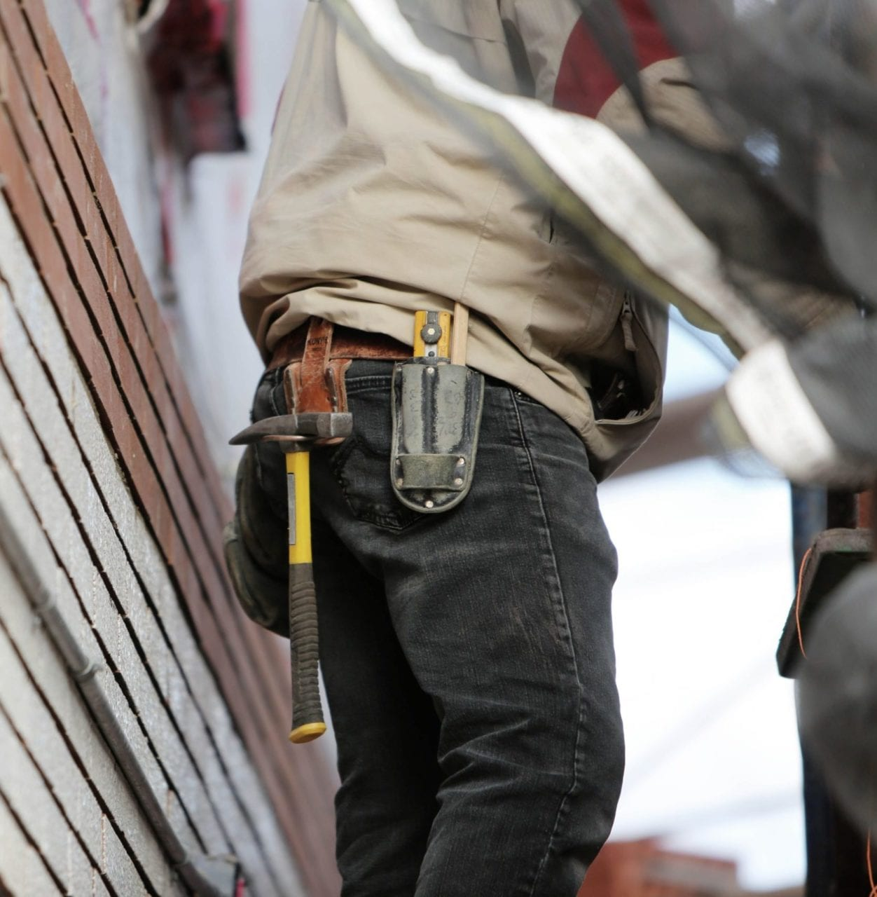 A construction worker with tools outside of a new home, highlighting the Builders Lien Act simplification