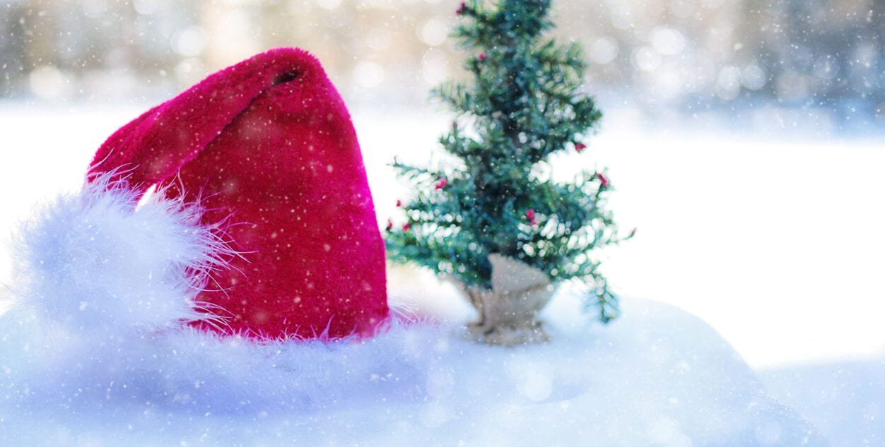 Santa's hat sitting on the snow next to a small christmas tree, highlighting the legal contract of a letter to santa