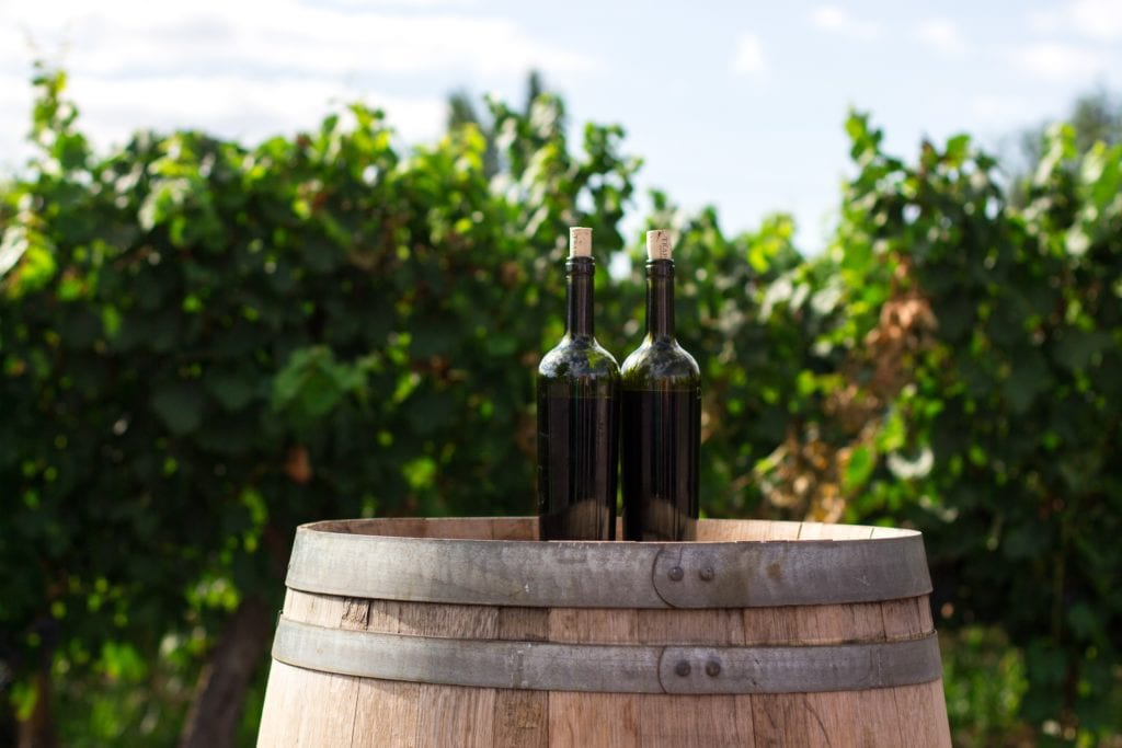 Two wine bottles on a wine barrel in a vineyard pertaining to Kelowna wineries and wine tastings for business professionals.