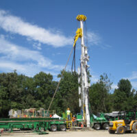 Schramm T130XD telemast drill outside in front of tall trees.