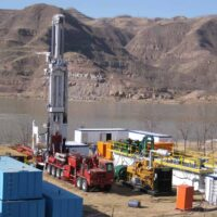 Schramm T200XD drill rig on-site next to a lake.