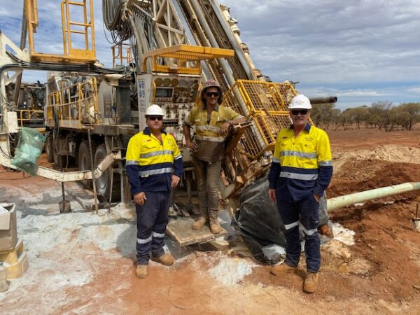 Three workers in the field next to drilling equipment pertaining to Schramm Value-add services.