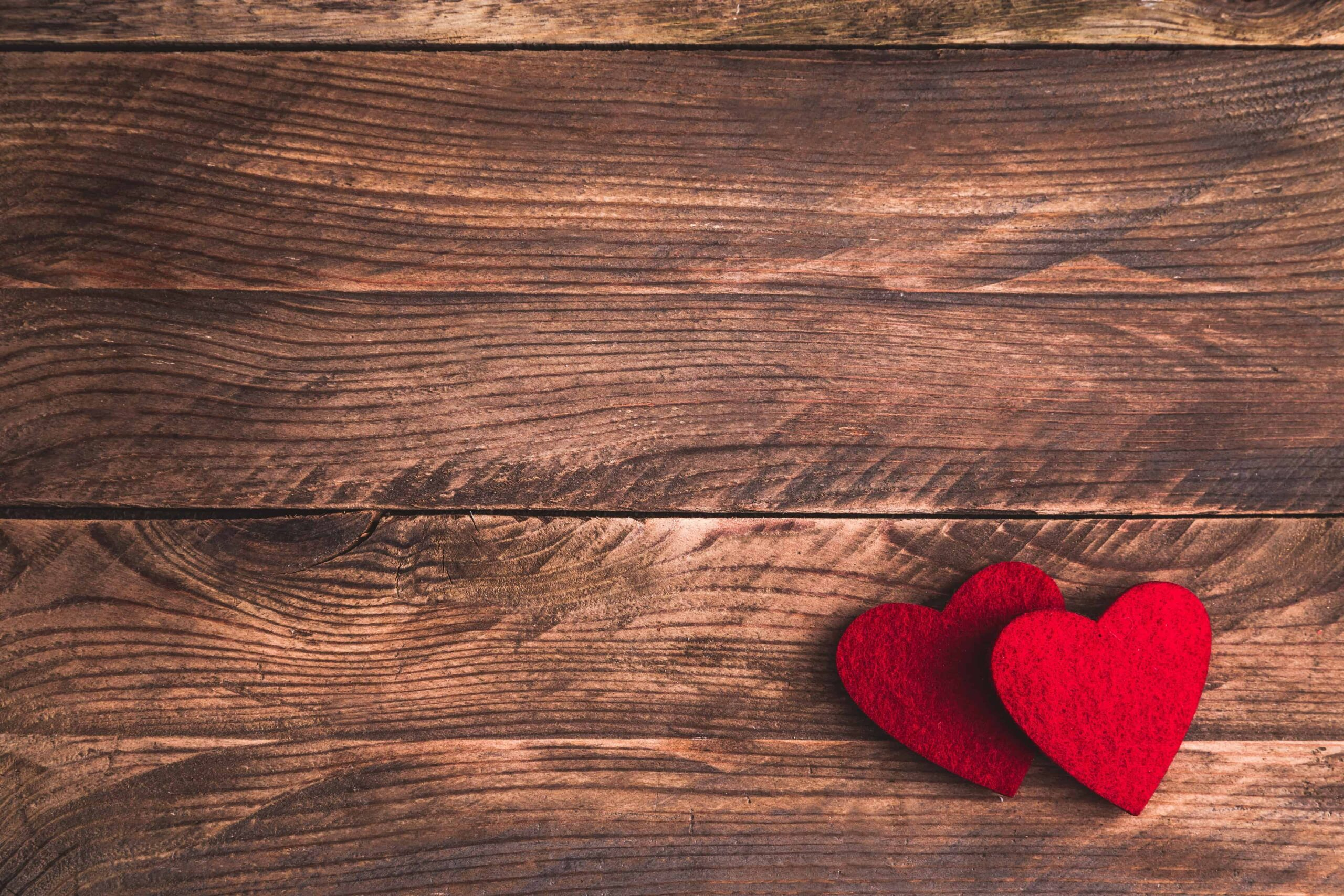 Valentines wooden background with felt hearts. Flat lay.