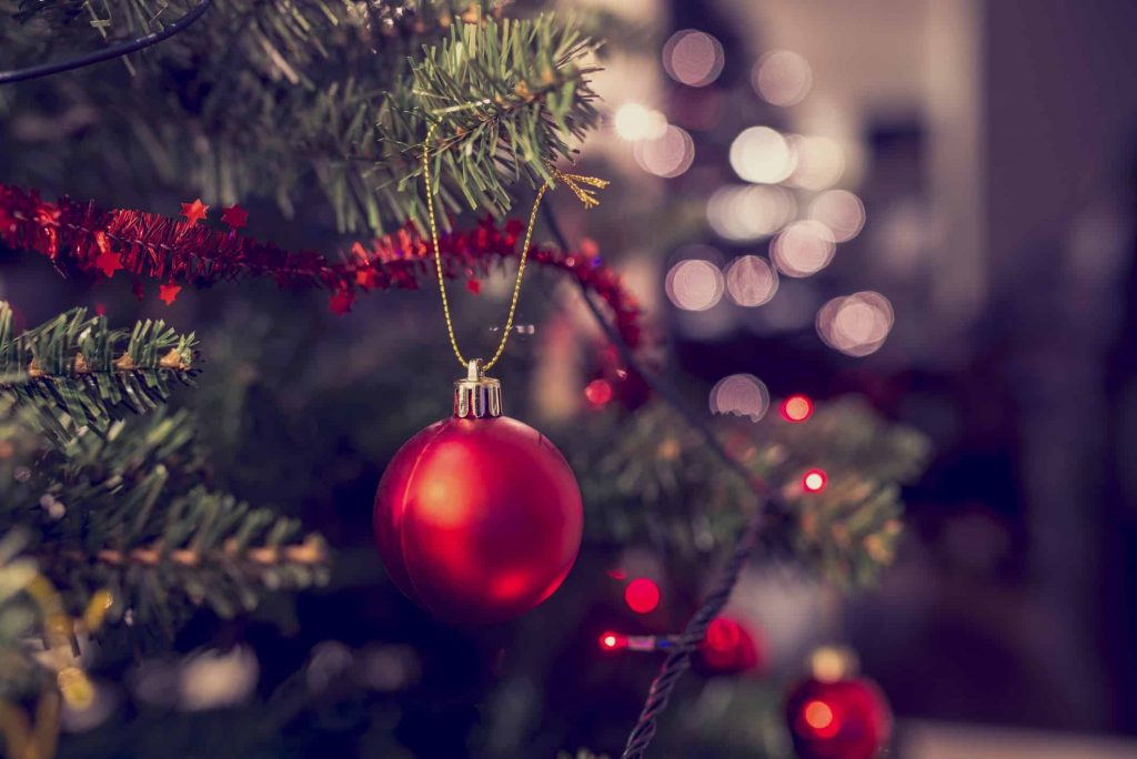Closeup of red bauble hanging from a decorated Christmas tree. Retro filter effect.