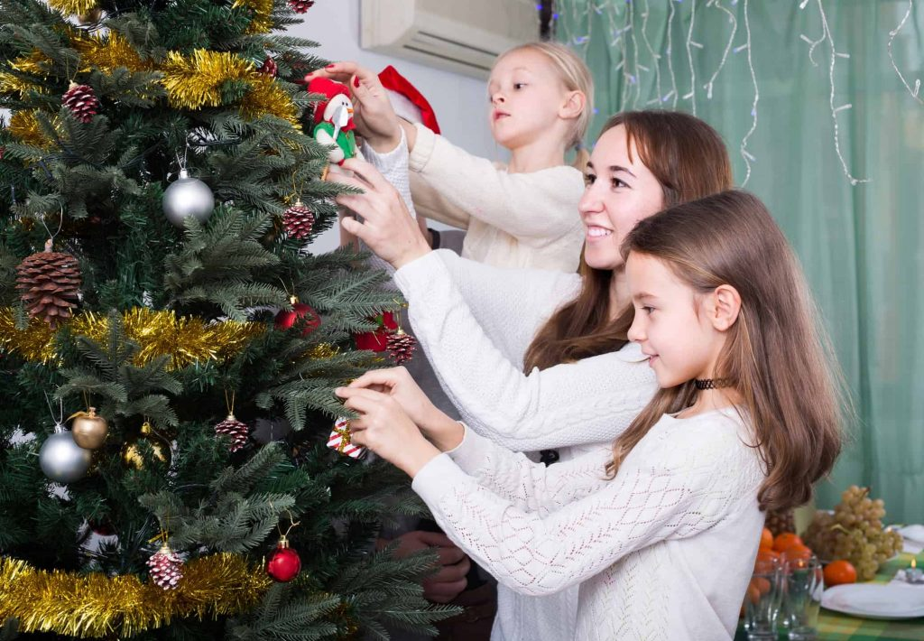 Cheerful united family with little daughters decorating Christmas tree together at home. Focus on girl